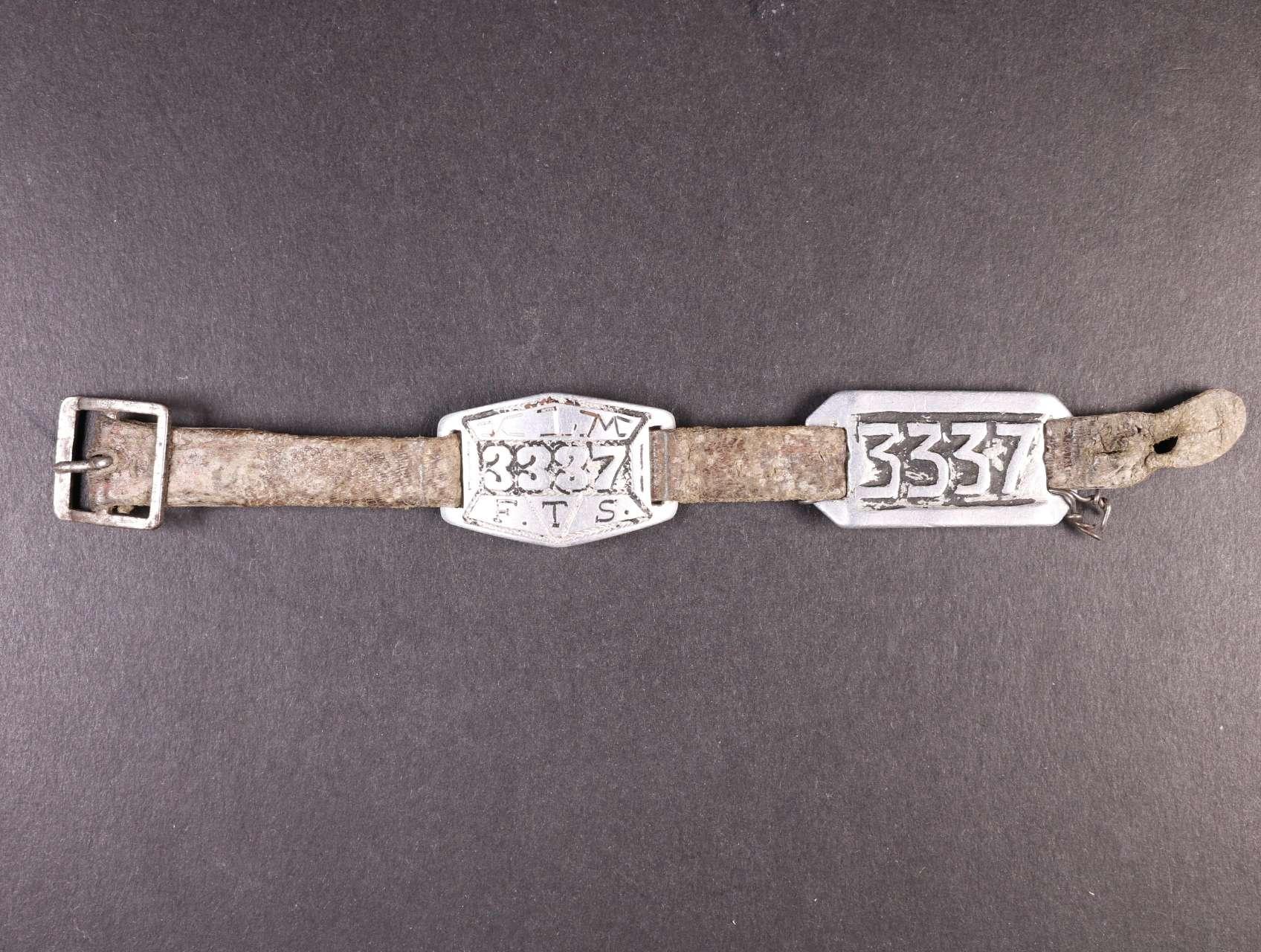 Terezín - kožený pásek na ruku se dvěma kovovými štítky - na prvním vyražen nápis K.L.M. a číslo 3337, pod tím písmena F.T.S. (Festung Theresienstadt), na druhém štítku vyraženo číslo 3337, zajímavé